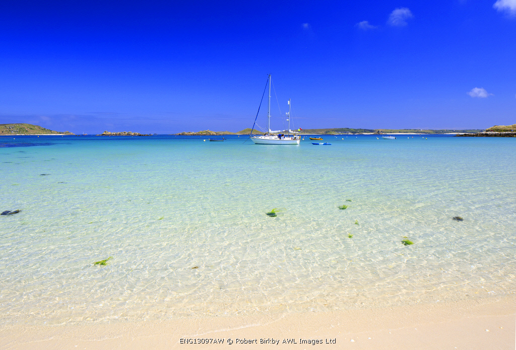England, Isles of Scilly, Tresco. A sailing boat at Green Porth beach.